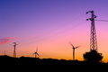 Wind turbines and electricity pylons silhouettes Stock Photos