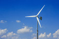 Wind turbines generating electricity on blue sky background Stock Photography