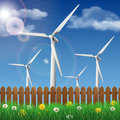 Wind turbines on a grass field behind a wooden fence Royalty Free Stock Photo