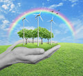 Wind turbines, grass and trees in human hands over green grass w