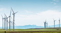 Wind turbines on green field over blue sky rows of boundless fields background of cloudy and distant hills alternative energy Royalty Free Stock Images