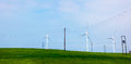 Wind turbines on a green hill group of three with power lines in the background Royalty Free Stock Photography