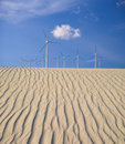 Wind turbines over sand dunes digital composite image of large rippling Royalty Free Stock Photos