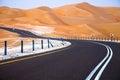 Winding black asphalt road through the sand dunes of liwa oasis united arab emirates in Stock Image