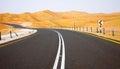 Winding black asphalt road through the sand dunes of liwa oasis united arab emirates in Royalty Free Stock Photos
