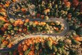 Winding mountain road trough the forest in the autumn with cars Royalty Free Stock Photo