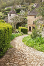 Winding stone path to stone cottage down in lush green spring foliage Stock Image