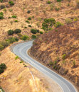Winding tarred road in the countryside snaking through dry hilly terrain viewed from above Stock Photography