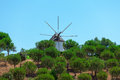 Windmill above a plantation of trees on farm with its sails or vanes visible against the blue sky Stock Image