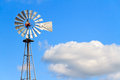Windmill and cloud an old stands tall against a blue sky with a puffy white excellent text friendly copy space Stock Image