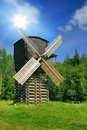 Windmill in forest under sun Stock Images