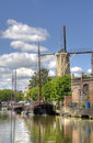 Windmill in gouda holland and historical boats a canal Stock Photo