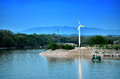 Windmill near a river blue sky pond water mountain Stock Photography