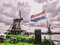 Windmill with netherlands flag in foreground at zanse schans Stock Photos