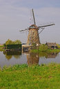 A windmill next to a house in kinderdijk with beautiful weather & water reflection Royalty Free Stock Photo