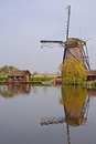 A windmill next to a house and tree in kinderdijk with beautiful water reflection Royalty Free Stock Photo