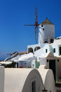 Windmill in oia santorini white houses and blue sky greece Stock Photo