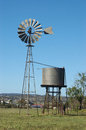 Windmill in paddock and tankstand queensland australia windmills are commonly used for pumping water from bores or dams to troughs Royalty Free Stock Photo