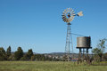 Windmill in paddock and tankstand queensland australia windmills are commonly used for pumping water from bores or dams to troughs Stock Images