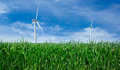Windmill power generator green grass blue sky Stock Photo