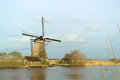 Windmill with reflection in the water landscape winter at kinderdijk netherlands Royalty Free Stock Photo