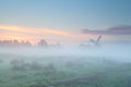 Windmill silhouette in dense morning fog Royalty Free Stock Photo