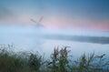 Windmill silhouette in dense sunrise fog Royalty Free Stock Photo