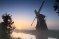 Windmill sunrise traditional during a foggy summer in the dutch countryside Royalty Free Stock Images