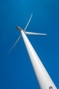 Windmill turbine green energy modern wind providing view from above and back large wings photo made against intense and clear blue Royalty Free Stock Image