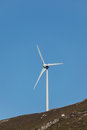 Windmill turbine silhouetted against blue sky Royalty Free Stock Photo