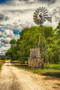 Windmill and Water Tank by a Country Lane Royalty Free Stock Photo