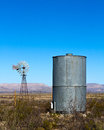 Windmill water tank old fashioned and watertank on flat dry land to provide to homestead in rural western texas Royalty Free Stock Images