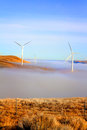 Windmills above clouds on brown hillside some in eastern washington generating electricity blue sky Royalty Free Stock Photo