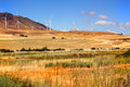 Windmills over countryside generating electricity stand as sentinels the in eastern washington state under clear blue sky Royalty Free Stock Photography