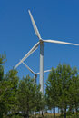 Windmills surrounded by woods generating clean energy Royalty Free Stock Images