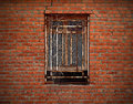 Window on aged brick wall wreathed with dried ivy Stock Photo