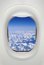 Window of an airplane from inside, view on snowy mountains Royalty Free Stock Photo