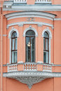 Window on the alcove pink facade of building with windows and bas relief from series of saint petersburg Stock Image
