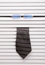 Window blinds tie and glasses sticking out of the Royalty Free Stock Photo