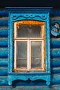 Window of blue cottage in russian traditional style with beautiful carved wooden frame and yellow sealing foam Royalty Free Stock Photo