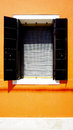 Window in burano on orange wall building architecture venice italy Royalty Free Stock Photography