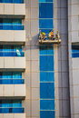 Window cleaners in a gondola cleaning the windows Royalty Free Stock Photo