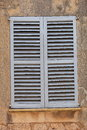 Window with closed wooden shutters slatted for safety and privacy in the exterior wall of an old building Royalty Free Stock Photography