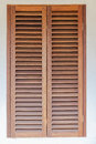 Window covered solid wood shutters fiited house Stock Image
