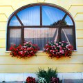 Window decorated with two baskets of red flowers Royalty Free Stock Photo