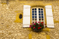 Window flowers stone facade Monpazier Royalty Free Stock Images