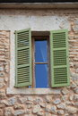 Window with green wooden shutters half open in a stone building walls made of natural rocks Stock Photos