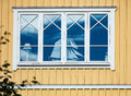 Window of a house with a model sailing boat reflection blue sky Royalty Free Stock Photos