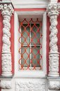 A window in a lattice between two symmetrical columns Royalty Free Stock Photo