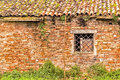 Window with lozenge grate in ruined house shaped rusty brick wall of cotignola italy Stock Photo